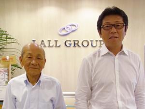 LALLグループ本社受付前にて。右がグループ代表の原川久司さん、左がヒューマネクス代表取締役の田口守さん