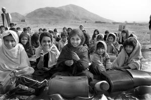 青空教室でランドセルを机代わりに授業を受ける小学生。日本の支援による使用済みランドセルが村の子供たちの就学率を上げている。