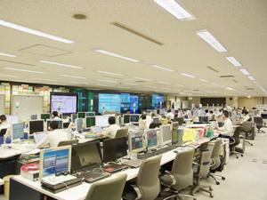 東京消防庁内の総合指令室内の様子。広大な室内には最新のICTを駆使した災害救急情報システ ムが配され、前面には大画面モニターが設置されている