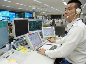 佐藤主任の席は電話対応する12名の後方に位置。常に通報される情報をシステム画面と音声で 把握、状況に応じて助言を行う